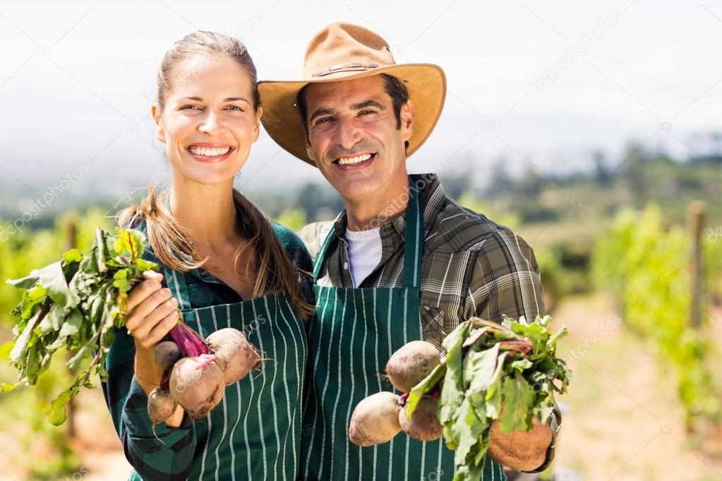 couple holding leafy vegetables